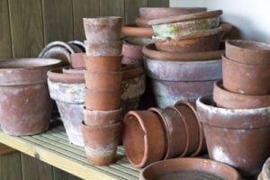 terracotta pots in several sizes and ages are piled together