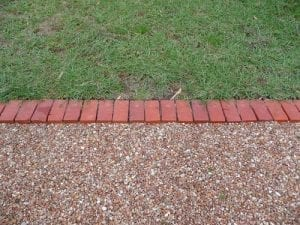 brick edging made with bricks lined side by side to separate the grass from the path