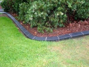 linked black bricks separate lawn from garden bed
