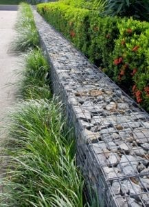 a gabion wall is built with stones filling the cage as a garden edge