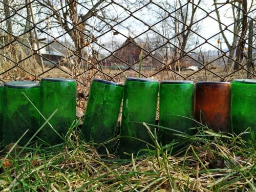 green bottles with buried necks make a garden edge