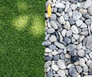Small river stones lie along a straight line of grass