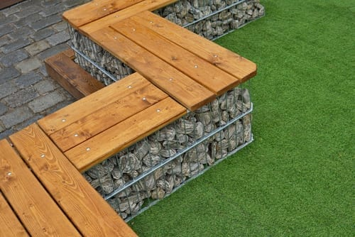gabion wall filled with rock has a wooden bench on top