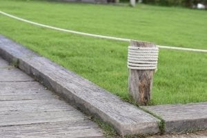 railroad ties make a yard edge separating the wooden path from the grass