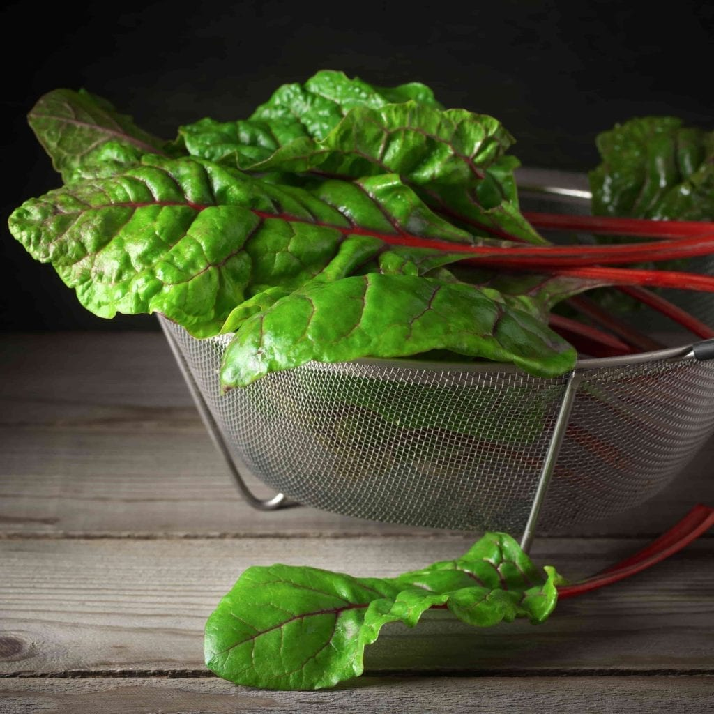 swiss chard green leaves with red stems in metal colander on wood table