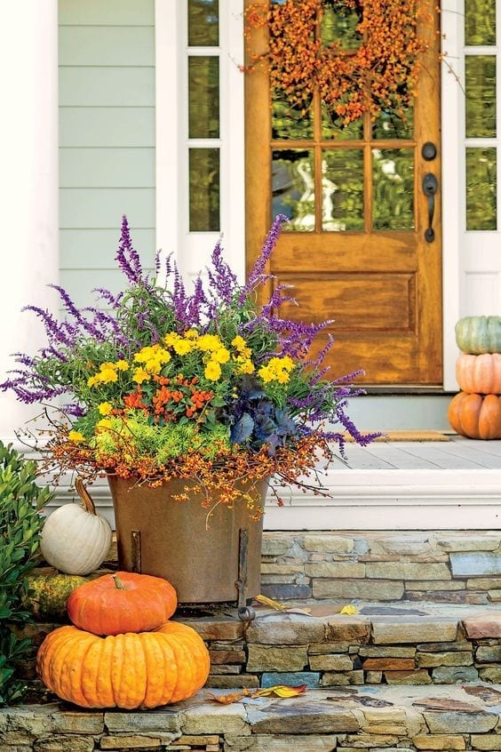 fall planter with purple astilbe, yellow mums,
