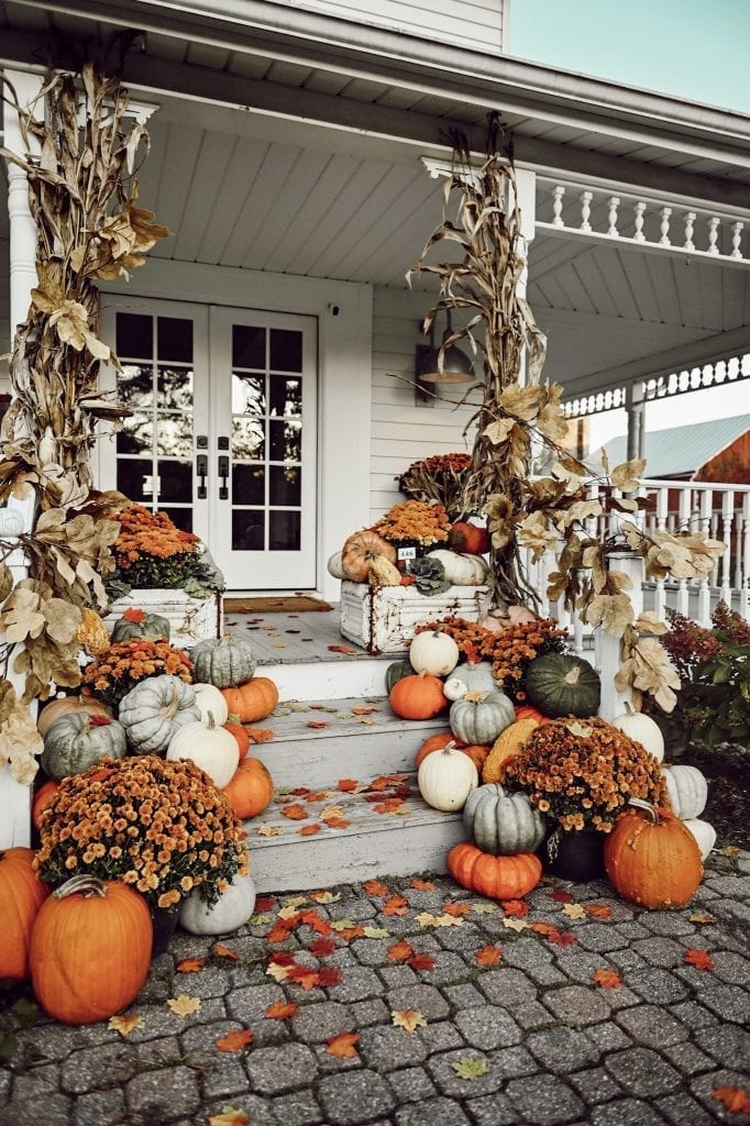 front porch decorated with fall harvest, pumpkins, cornstalks