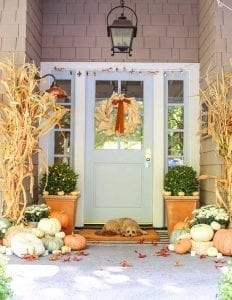 front porch decorating with soft fall colors, pumpkins, cornstalks