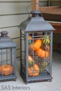 gray lanterns filled with small pumpkins for fall