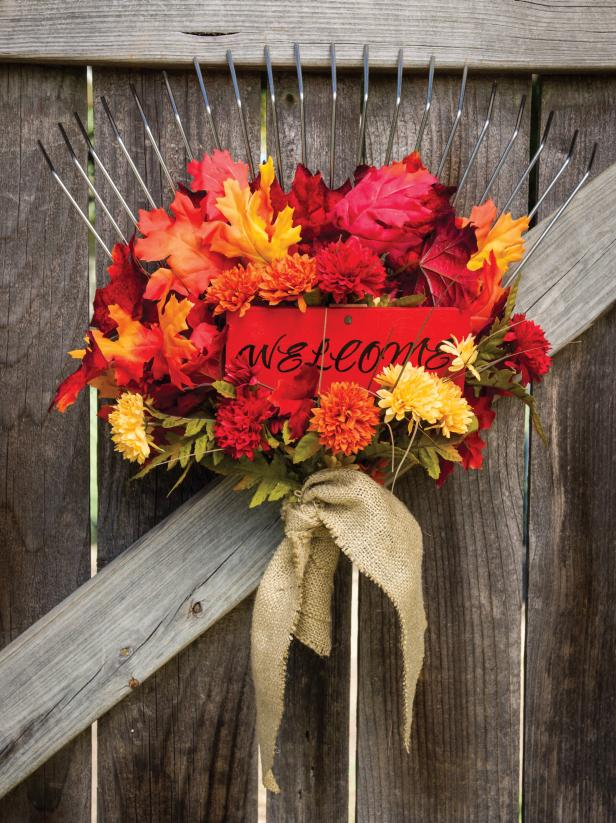 wood gate decorated with rake and red, orange, yellow fall decor