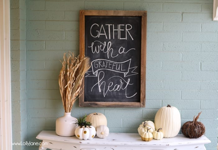 fall decor chalkboard and faux pumpkins on a white table