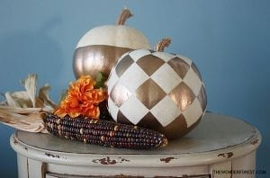 two pumpkins painted with white and gold paint on a table
