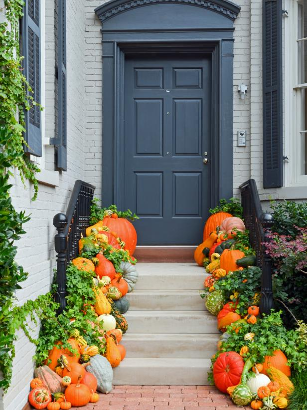 Front porch fall decor lined with pumpkins and gourds