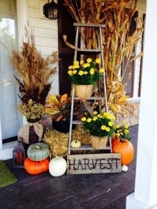 porch with fall decor, ladder, pumpkins, sign