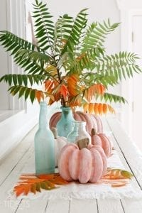 white wash pumpkins and pair with blue vases and fall foliage