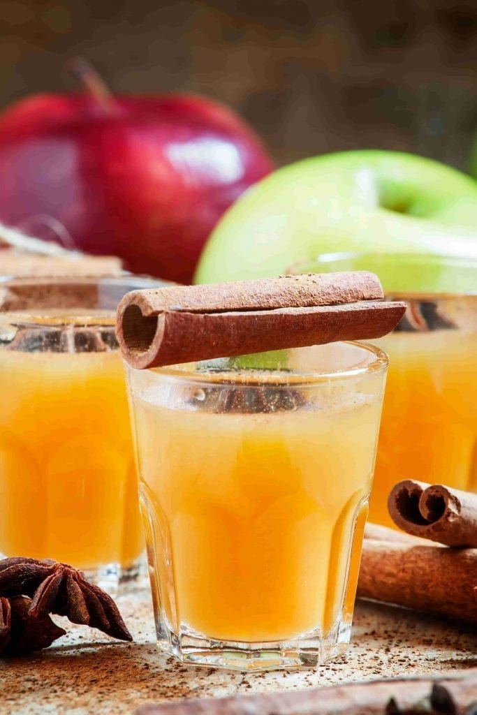 apple cider in glasses with cinnamon stick