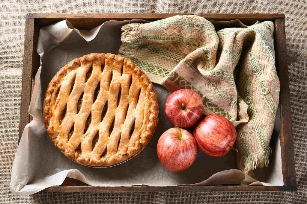 apple pie next to fresh apples in wood box