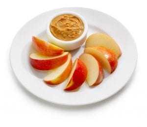 short-term storage of fresh apple slices with peanut butter on white plate