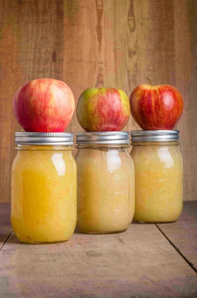 jars of homemade applesauce with apples on top of the jars