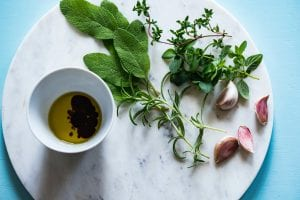 fresh herbs sprigs spread out on a plate with a dish of olive oil