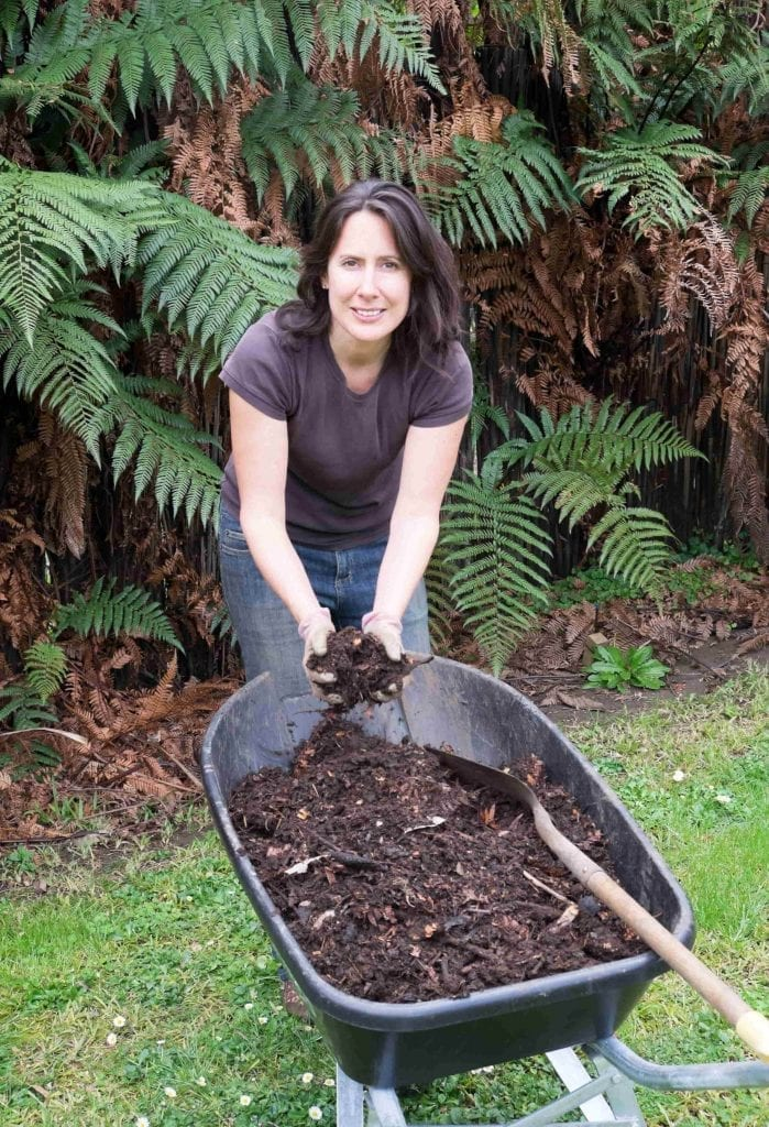 woman with wheelbarrow filled with compost