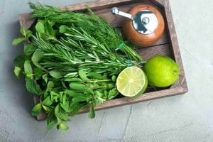 fresh herbs on wood tray with pepper grinder and lime