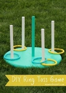 DIY ring toss game with stakes and rings on turquoise base sitting on grass