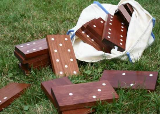 DIY dark brown dominoes with white spots in white bag on yard
