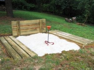 DIY horseshoe pit white sand enclosed in brown wood in yard