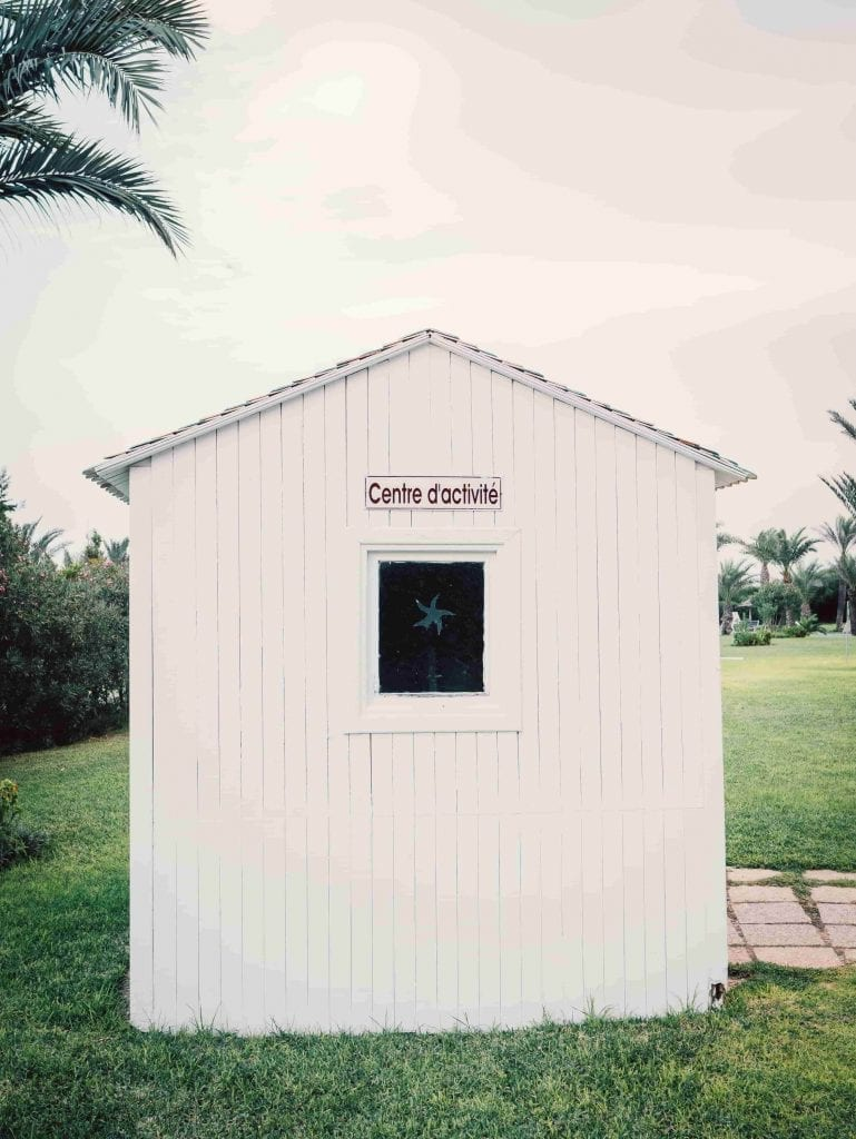 small white tool shed on green grass