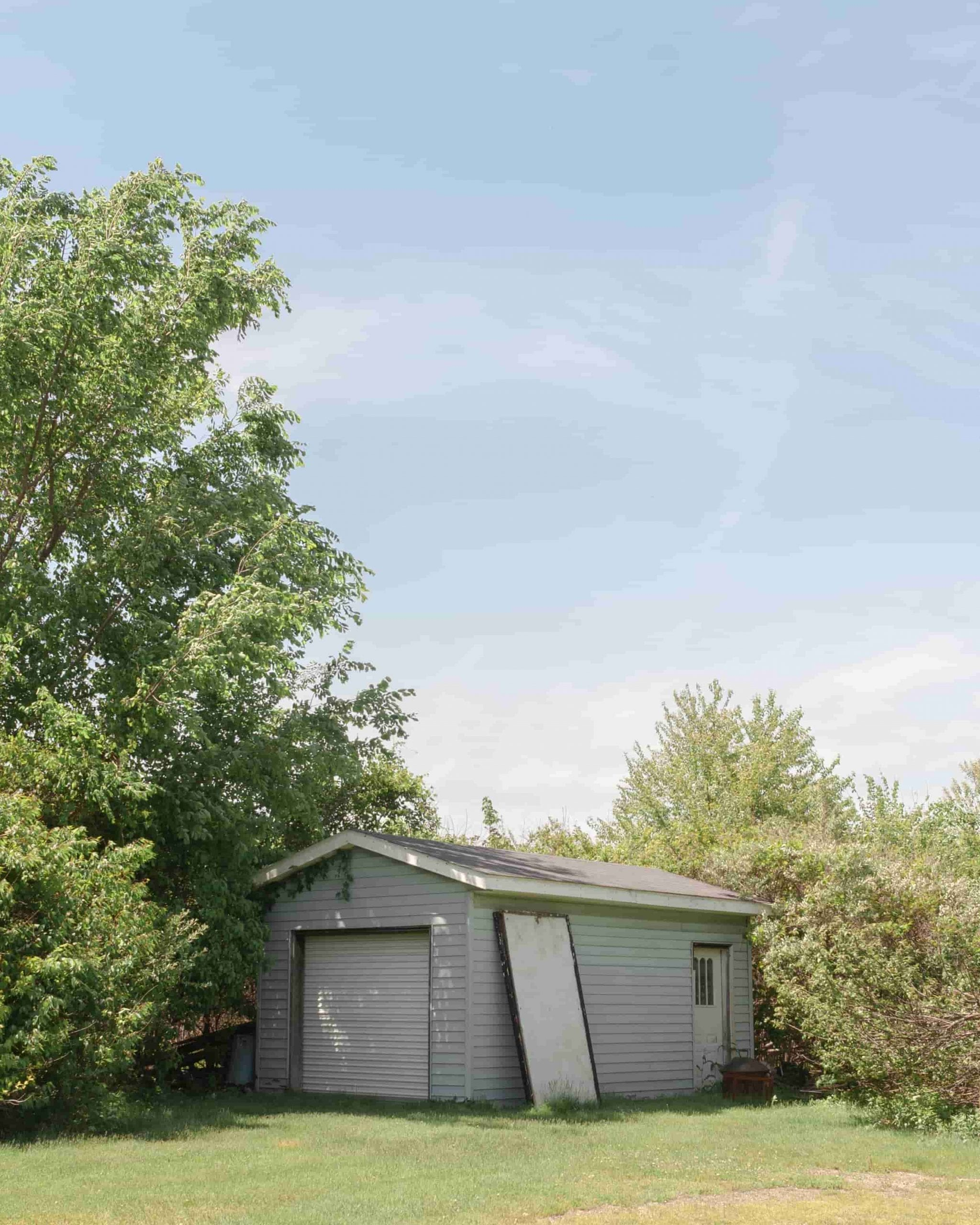 small gray shed with white door at back corner of property